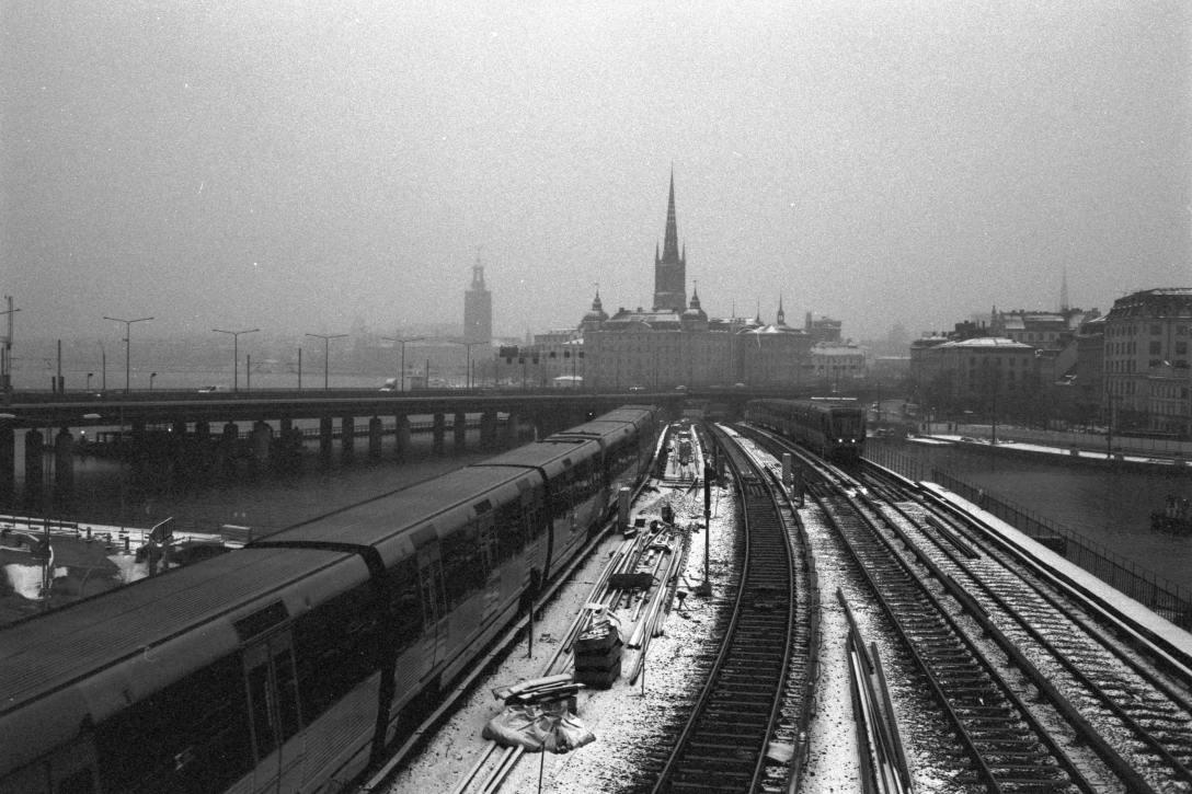 Fotografia preto e branco, vista aérea da paisagem da área central de Estooolmo com trilhos de trem e prédios ao fundo